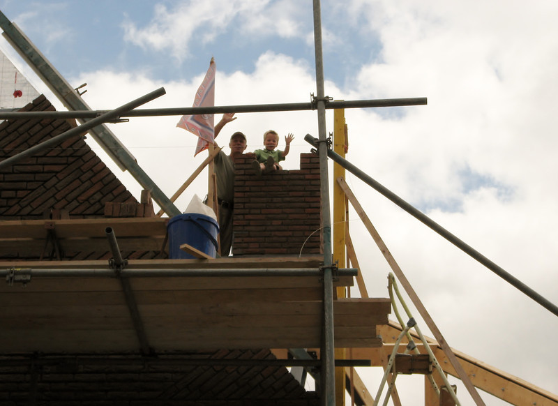 Stijn and Marijn waving from the highest spot of the house