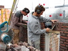 "Paul and Twan bricklaying the upright courses (NL: ""strekse boog"") of the gable"