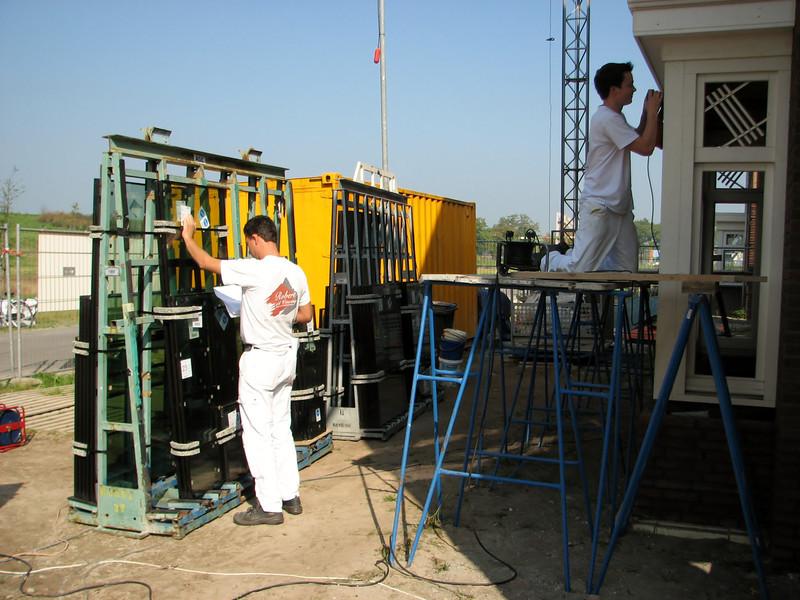 Robert inspecting the measurements of the window-pains and Rick working on the bay (firm Robert van de Wetering)