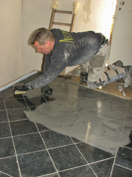 Toine Adriaans is washing in the hall floor (bluestone) (Avedo tegelwerken)