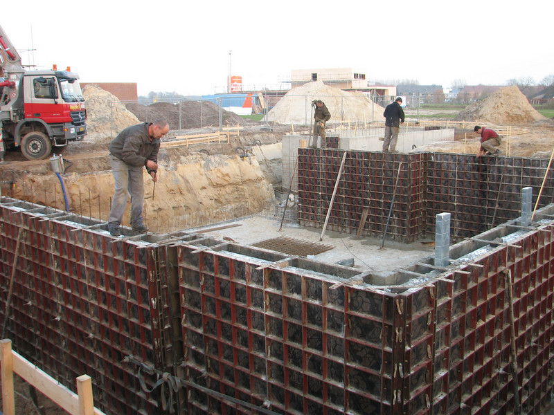 Team work, pour concrete of the main cellar, measure, vibrate and reinforce the wall