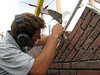 """Paul bricklaying the upright course (NL: """"boerenvlecht"""") of the gable top"""