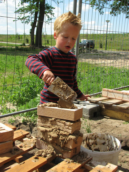 Stijn bricklaying with mud on the building site