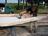 Hans sawing and fit the insulation boards with a chain saw