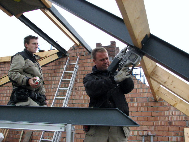 Hans drilling holes to assemble a steel beam for an attic