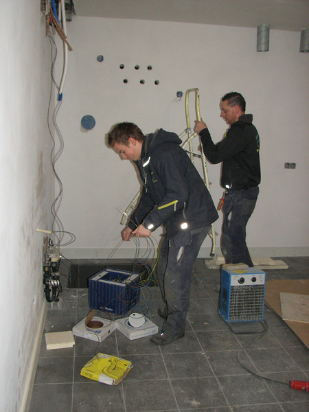Electrician Martijn Fassbender and Niels are pulling the electrical wires