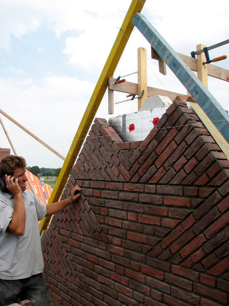 "Paul bricklaying the upright course (NL: ""boerenvlecht"") of the gable top"