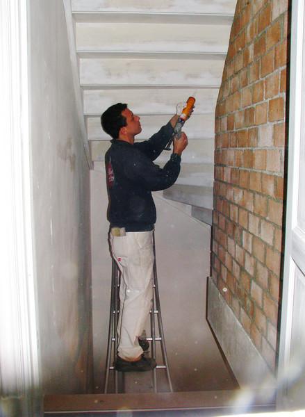 Robert is sealing the back side of a stair (firm Robert v.d. Wetering, schilder- en glaswerken)