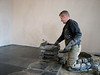 Toine Adriaans tiling the kitchen floor with bluestone (Avedo tegelwerken)