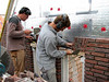 "Paul and Twan bricklaying the upright courses (NL: ""strik"") of the gable"