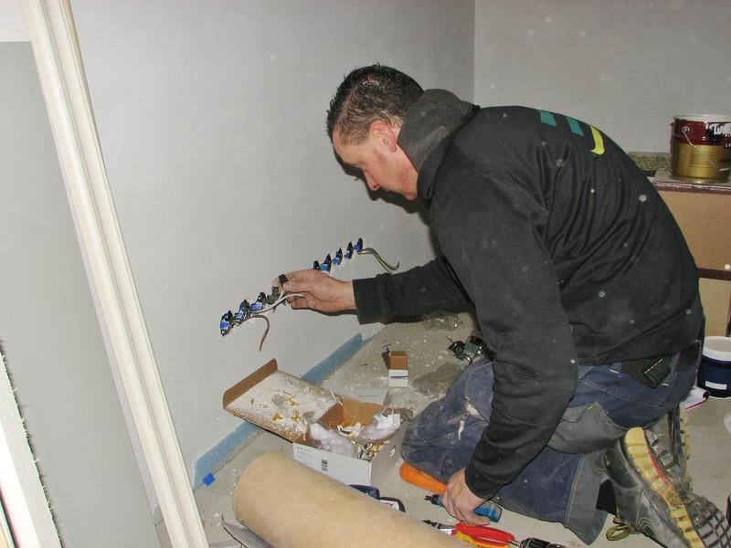 Electrician Martijn Fassbender is mounting the sockets