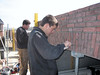 Twan and Erik bricklaying the bricksupright course of the garage door (width 2,5 m. R 3,75m.) (NL: strekse boog voor de garage deur)