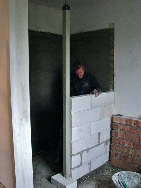 Toine Adriaans, the tiler, bricklaying the Ytong douche wall