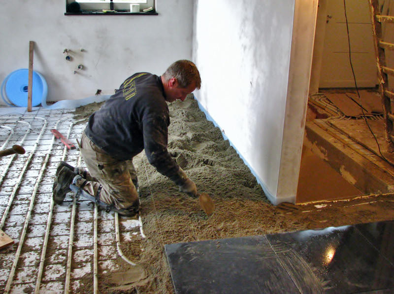 Twan tiling the kitchen floor with bluestone (Avedo tegelwerken)