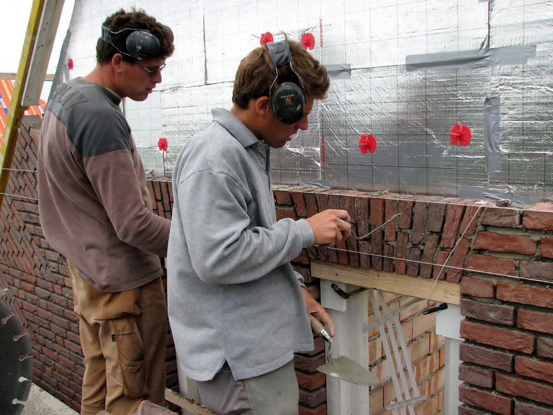 """Paul and Twan bricklaying the upright courses (NL: """"strekse boog"""" of """"strik"""") of the gable"""