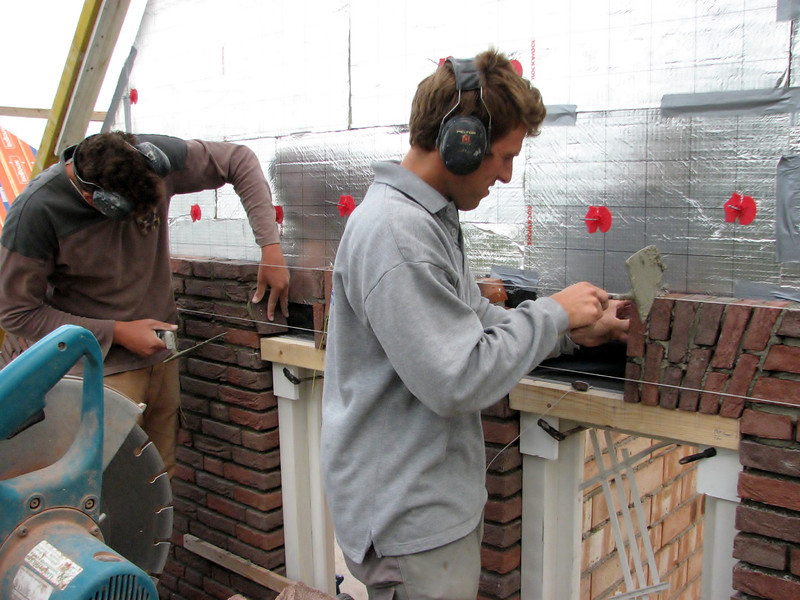 "Paul and Twan bricklaying the upright courses (NL: ""strekse boog of strik"") of the gable"