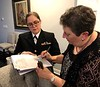 ENS Jennifer Edwards assists Linda Rakers, niece of Uncle Billy, sign paperwork, confirming safe receipt of his remains.