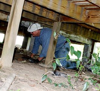 Warren Johnson works under the home of Rosemary Faulks in Andersonville. 10-7-2011