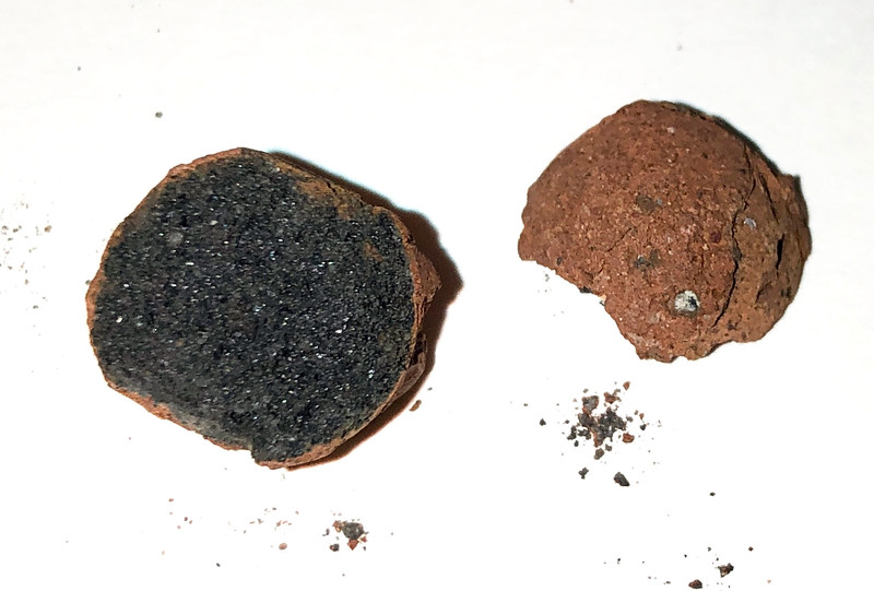 These balls are very light and seem to be made from a pumice type mineral material.  Each is covered with a reddish coating.  Guesses have included Sling shot ammo, fossilized bunny turds, and ossified alien gonads.  However, likely they are hydroponic substrate balls, used to grow plants.  In this case, being so remote, perhaps growing California's biggest cash crop!