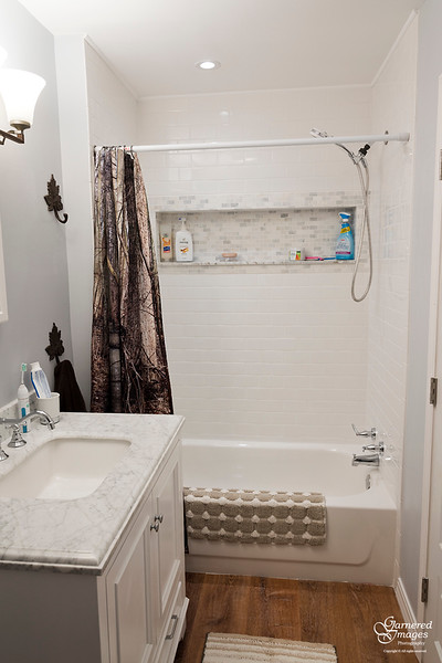 September 23, 2018:  Second floor bathroom after.  Behind the curtain:  new tub, fresh tile, marble inset shelf, and a light.
