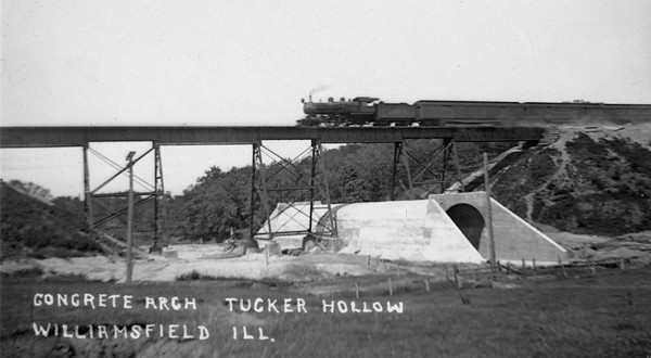 2020.017.06--david conrad collection RPPC--AT&SF--steam locomotive on passenger train crossing steel bridge over concrete culvert in Tucker Hollow looking southeast from north side of track--Williamsfield IL--no date