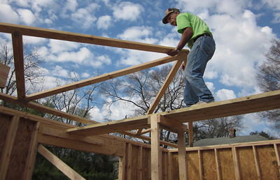 One of the construction leaders, Charlie Thell, pulls a truss onto the roof in Lumpkin, Ga.