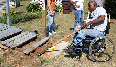 Thad Harris, right, helps repair a wheelchair ramp.