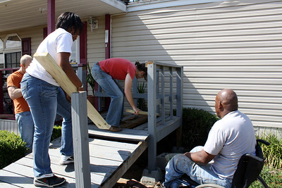 Thad Harris, right, helps volunteers as they repair a wheelchair ramp.