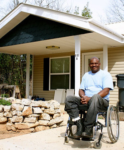 Thad Harris poses in front of his home just before it was finished. The energy efficient home's average monthly power bill in his first year living there was just over $49, which was a great help on his limited income.