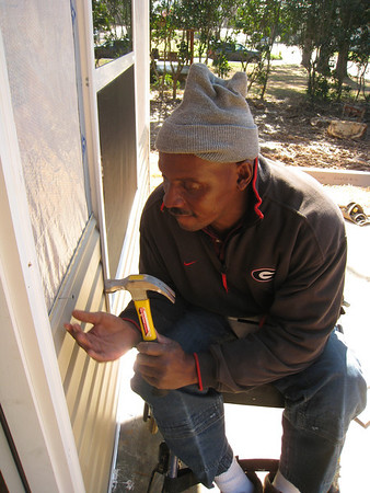Thad Harris helps put vinyl siding on his home.