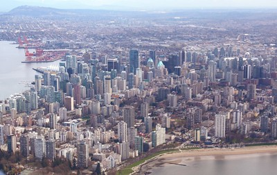 Looking east-southeast over downtown Vancouver and the main dockyards.  Capitol Hill is at upper left. Note the triangular region of blue-green buildings on the left side of downtown.