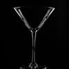 Cocktail glass with dark field lighting on black acrylic.