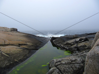Tide pool and crashing waves, Peggy's Cove, Nova Scotia.