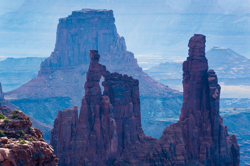 """Washer Woman Arch is both a """"desert tower"""" and an """"arch"""". The name no doubt derives from the resemblance of this spectacular formation of a tall and slender woman reaching her hands (which form the arch) into a tub. Located in Canyonlands National Park, it sits atop a ridge flanked by Monster Tower to the south and a rarely climbed Sandcastle to the north."""