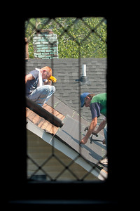 Two roofers as seen through a neighbor's window