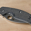 "This knife has ""twill woven"" peel-ply carbon fiber scales, which is really spectacular. It looks good, and isn't slick."