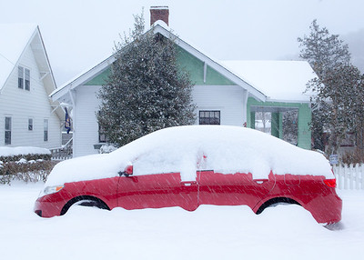 Snow covered house and car