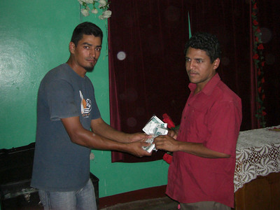 Preacher receiving seeds after completing agricultural seminar on How to Grow a Garden