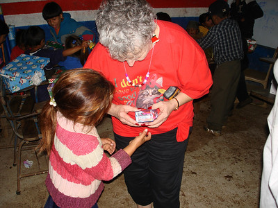 Helping child with toy from Smile box at St. Inez