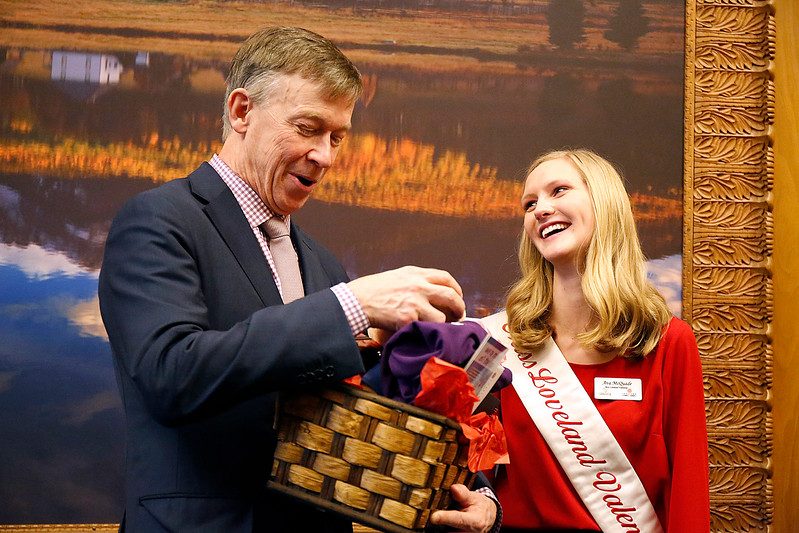 Miss Loveland Valentine Ava McQuade laughs as Colorado Governor John Hickenlooper comments on how his wife will want the stuffed bear from the gift basket she gave to him at the Colorado State Capitol on Monday, Jan. 12, 2018. (Photo by Lauren Cordova)