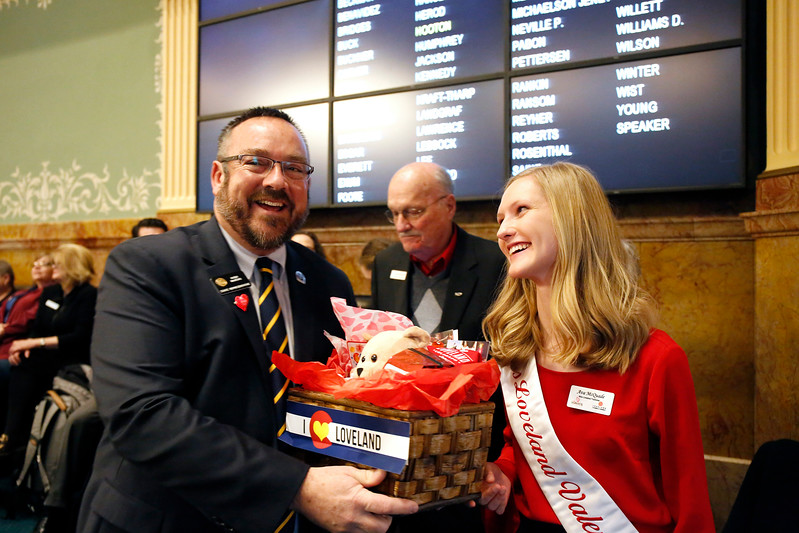 Miss Loveland Valentine Ava McQuade smiles as State Representative Hugh McKean accepts his gift basket on the House floor at the Colorado State Capitol on Monday, Jan. 12, 2018. (Photo by Lauren Cordova)