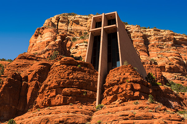 Chapel of the Holy Cross, Sedona, Arizona. Conceived by sculptor Marguerite Brunswig Staude in 1932. Her early sketches impressed Lloyd Wright, son of the famous American architect Frank Lloyd Wright, but were not approved by the archbishop of Los Angeles. Her initial ideas for the church changed in 1950 after she saw a church in France designed by the painter Georges Roualt. Lloyd Wright clung to the original plans and refused to work with her. Richard Hein was chosen as project architect, and the design was executed by architect August K. Strotz. It was completed in 1957.