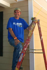 Andy measures the porch roof for gutters.
