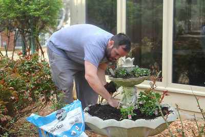 Charlie plants herbs in the old fountain. Lachance home by Donna Lachance 012
