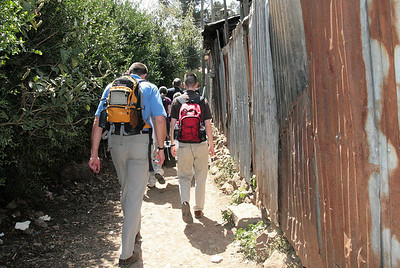 The American team takes a walk through an alley way to visit team member Alemnesh's home in Ethiopia.  The tin fencing is a common means of separation between properties.