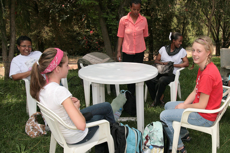 Americans and Ethiopians mingle among tables for conversation and meal.