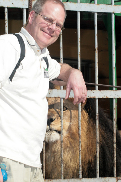 """<div align=""""left"""">We also stopped by the local Addis Ababa zoo. Here, Brad poses for a picture, and the lion sizes up a potential meal (Actually, the lion tried to take a swipe at him right after this shot, so Brad decided to put some distance between himself and the king of the beasts).</div>"""