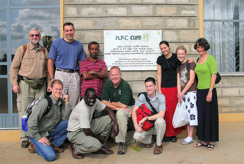 """Most of our team in front of <a href=""""http://www.helpcurenow.org/site/pp.aspx?c=nvI1IeNYJyE&b=3474787"""">CURE Ethiopia Children's Hospital (CECH)</a>.   """"The CURE Ethiopia Children's Hospital (CECH) is a pediatric orthopedic teaching hospital that will serve physically disabled people in Addis Ababa. CECH will fill a critical need for an orthopedic and trauma care residency program in Ethiopia. The hospital will treat disabilities such as cleft lip and palate, clubfoot, burn contractures, and other physical disabilities. The hospital will be a state-of-the-art 60 bed hospital complex that will provide modern medical and surgical care to physically disabled children in Ethiopia.""""  Even today, people with facial disfigurements may experience discrimination and social exclusion in Ethiopia. Individuals with a facial 'difference' may be ostracized by their communities, denied their right to a school-place, and in some cases are forced to become street-children.  During our visit to CURE I watched a cleft-lip correctional operation by Dr. Paul Lim, which was completed in about 45 minutes. Since the CURE hospital went """"on line"""" in 2008 Dr. Lim has performed over 400 such operations. That's over 400 lives changed for the better, 400 lives who experienced the love of Christ in a very tangible way. Please visit the CURE website via the link above, and consider making a donation to help this ministry of God's love advance.  Pictures of an actual clef-lip correctional operation can be viewed <a href=""""http://www.davidenglundphotography.com/Missions/Ethiopia/Cleft-Lip-Operation/11233952_Xe9G3#787839430_cekAv"""">here</a>."""