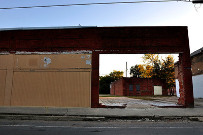 A store front wall left standing frames an empty building on the backstreets of Shaw.