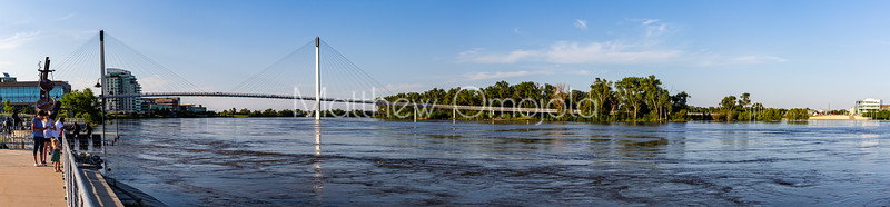 Panorama, Missouri river flood of 2019, Omaha Monument to Labor, submerged in flood water, Swollen Missouri river, Bob Kerrey foot bridge, Riverfront condominiums, Carl T. Curtis, Regional headquarters National Park service, on the left, Closed Park sign, City of Omaha,  Tom Hanafan river's edge plaza, Council Bluffs, Iowa flooded